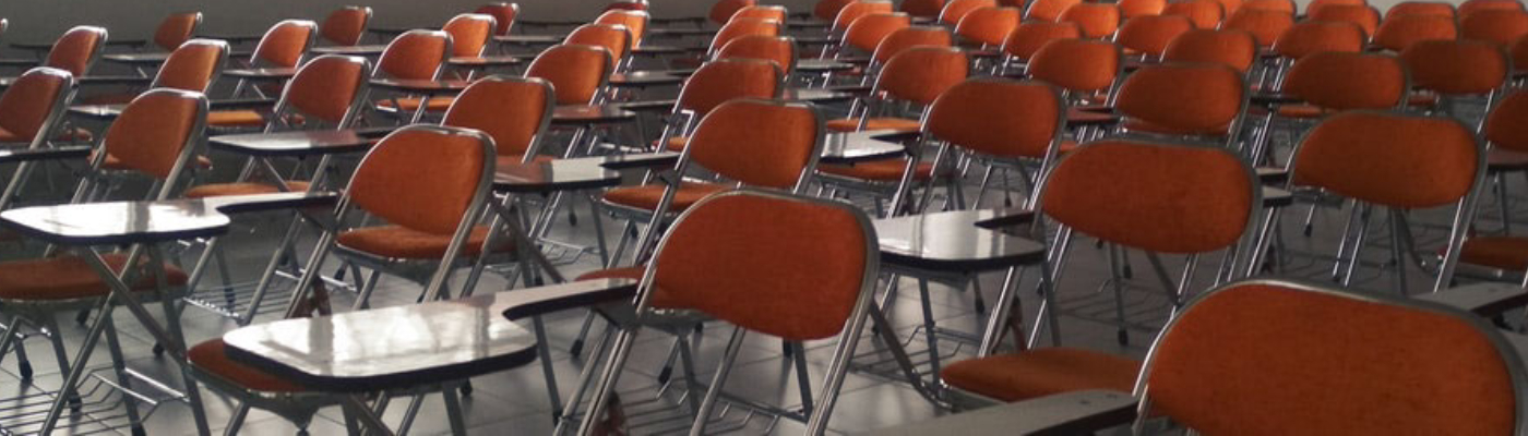 An empty classroom full of desks with orange chairs attached to them