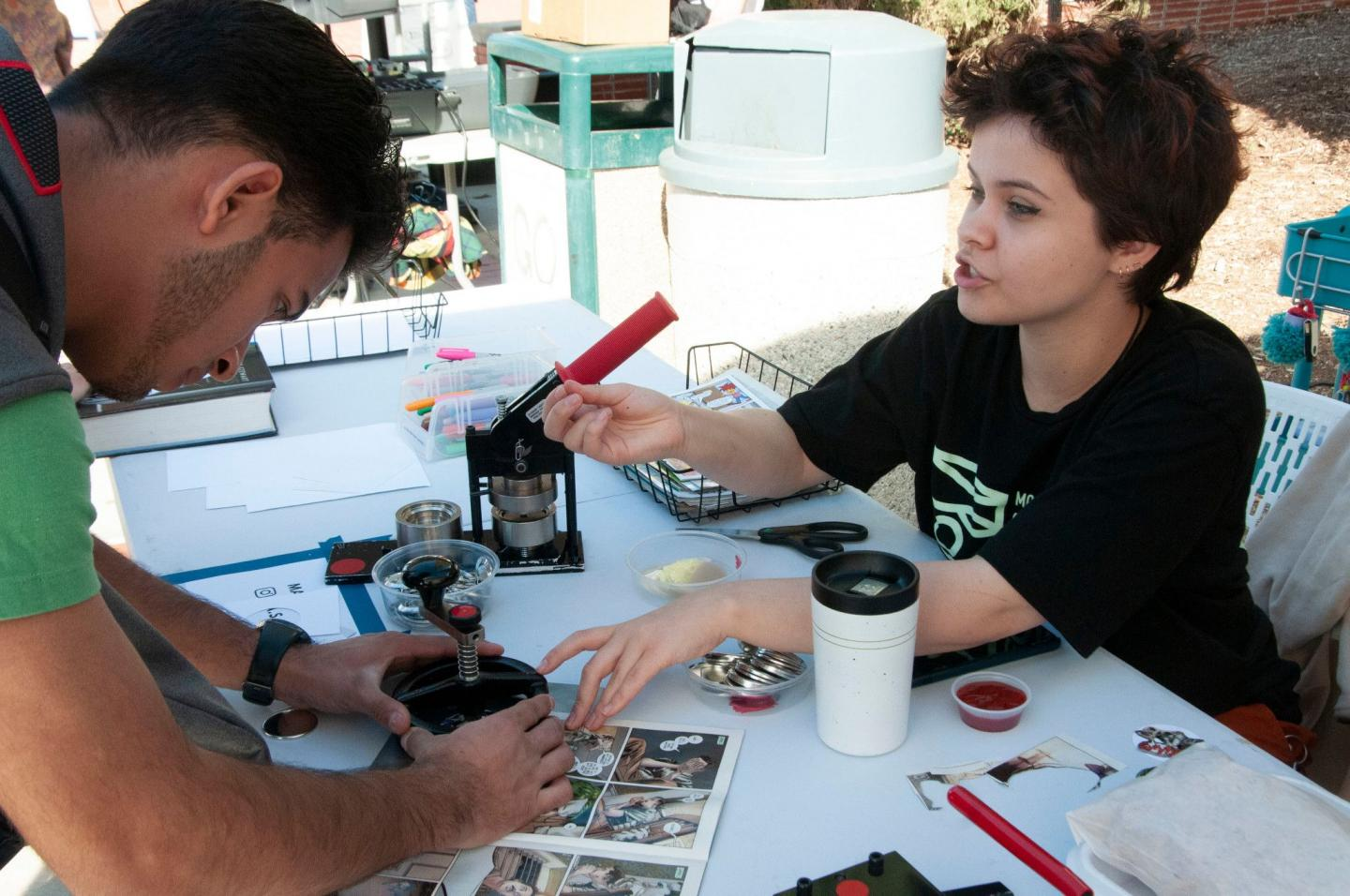 Moorpark College Club Rush, two students make buttons with comic book graphics