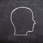silhouette of a head in white chalk on a blackboard