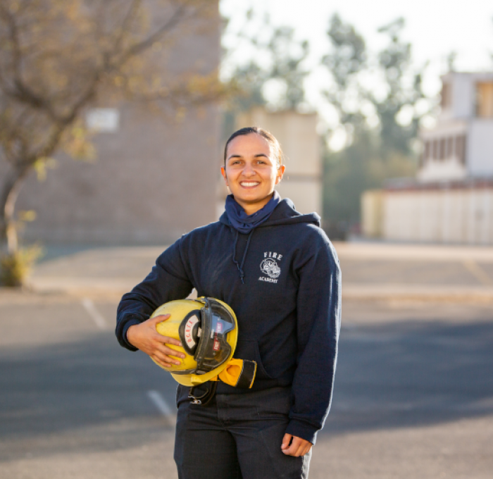Female Fire Academy Student Holding Firefighter's Helmet